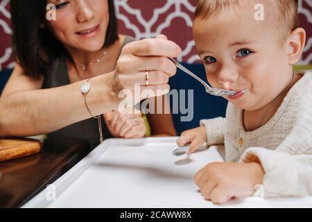 Primo piano di madre che alimenta il suo bambino, seduto in una sedia alta.