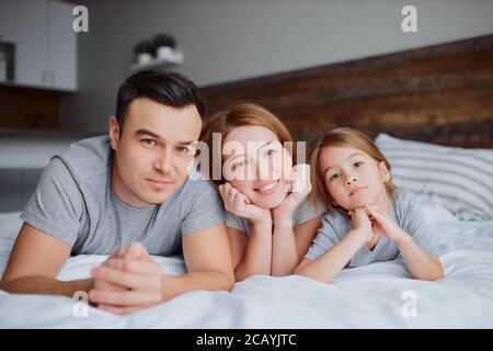 ritratto di bella famiglia felice che giace sul letto insieme, madre padre e bambina baciare abbracciando e ridendo. al chiuso