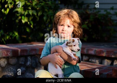 Bambini tristi con cane misto chihuahua. Capretto abbraccia amorevolmente il suo cane animale domestico. Foto Stock