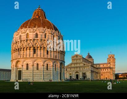 Pittoresca vista del Battistero di San Giovanni in primo piano, del Duomo al centro e della Torre Pendente sullo sfondo a destra,...