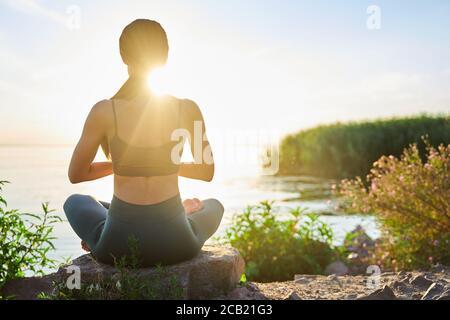 Giovane donna sportiva che medita sulla spiaggia nelle prime ore del mattina Foto Stock