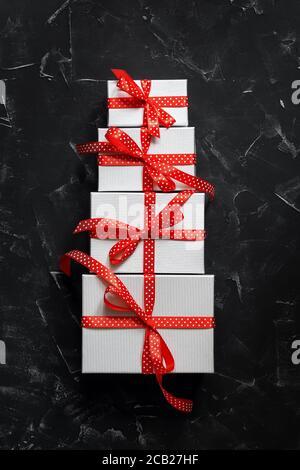 Torta astratta fatta da scatole regalo con un nastro rosso su uno sfondo di pietra nera. Vista dall'alto, disposizione piatta. Layout creativo