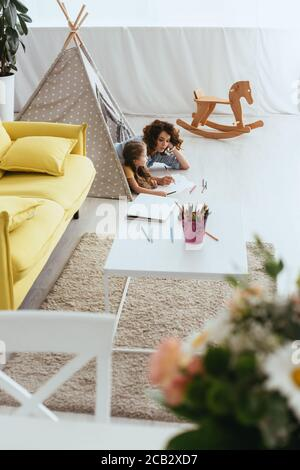 vista ad alto angolo di babysitter e disegno bambino mentre si sdraia nel giocattolo wigwam Foto Stock