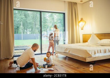 Genitori giovani con i loro bambini in camera. Madre e figlia, padre con figlio che gioca a terra. Generazione in crescita, concetto di famiglia
