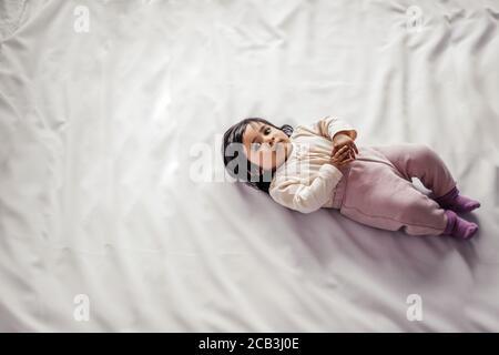 Adorabile bambina afro americana guardando la macchina fotografica mentre si sdraia su un comodo letto, vista dall'alto foto. Concetto di amore, spazio di copia