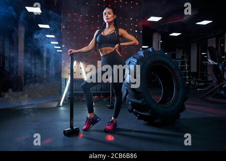 Donna muscolosa che tiene il grande martello vicino a ruota di pneumatico enorme, guardando via. Ritratto di bodybuilder femminile in posa in palestra, dopo un duro allenamento e guardando la macchina fotografica. Concetto di sport.