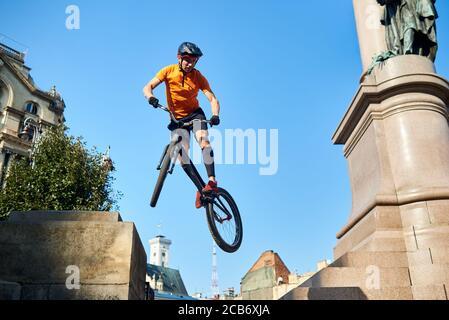 Vista da sotto l'uomo estremo che tiene in mano una bici sportiva e che pende in aria. Ciclista guardando giù quando fa trucco. Concetto di trucco.