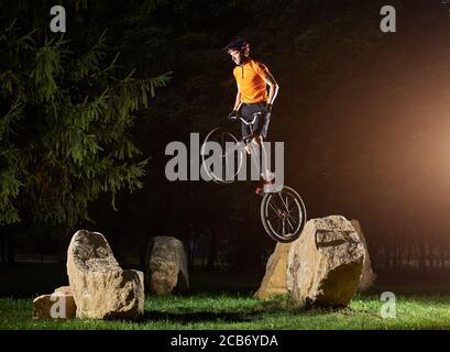 Vista laterale del ragazzo impavido che fa trucco mentre si sta in piedi su una bicicletta. Ciclista tenendo il manubrio in mano e facendo acrobazie sulla pietra. Concetto di movimento.
