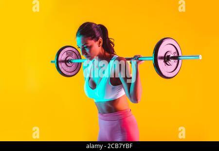 Donna allenarsi con barbells in palestra