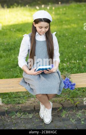 Elegante bambina scolastica con libro nel parco, lettura concetto di poesia. Foto Stock