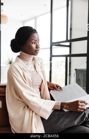 Foto di giovane donna africana piuttosto concentrata seduta sul divano in interni a casa durante la lettura di riviste o libri Foto Stock