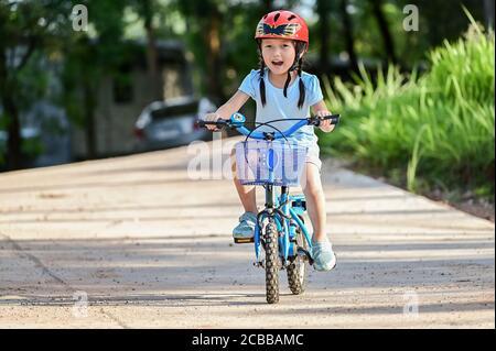 Ragazza felice che cavalcano una bicicletta nel parco del giardino. Bambino attivo che indossa casco da bici. Sport di sicurezza per il tempo libero con concetto di bambini Foto Stock