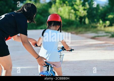 Felice madre insegnando piccola figlia a guidare una bicicletta. Bambini che imparano a guidare una bicicletta nel parco e bambini che indossano il casco da bici. Sport di sicurezza Foto Stock