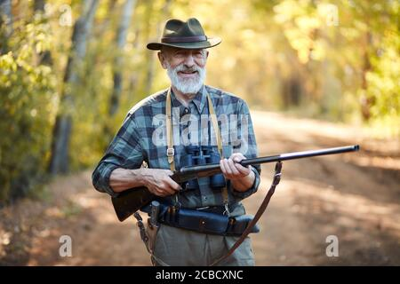 Ritratto di un cacciatore positivo che tiene la pistola, stare in foresta