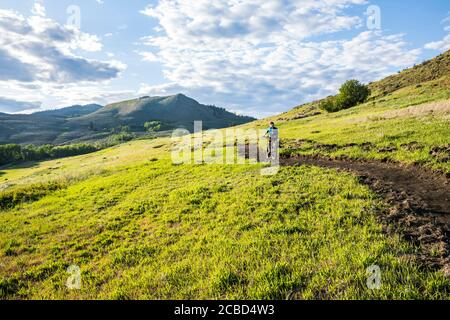 Una donna che sale sul sentiero di Lewis Butte fuori Winthrop, Washington in un pomeriggio soleggiato a maggio.
