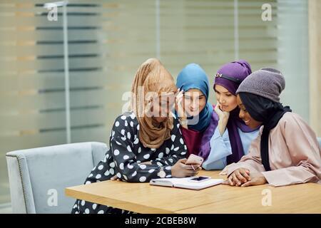 Blogger islamica di viaggio che condivide informazioni da smartphone con lei seguaci seduti in un gruppo di quattro persone nella hall dell'hotel