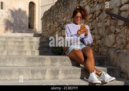 Ritratto di una giovane donna nera attraente che prende un selfie con il suo cellulare. Parlare al telefono seduto sulle scale Foto Stock
