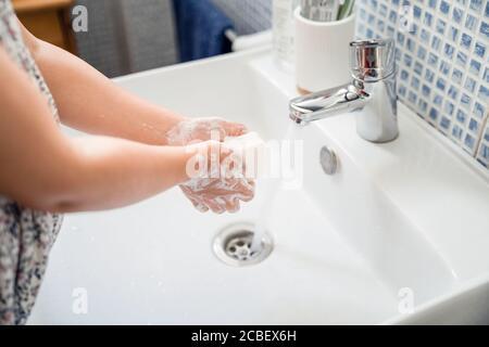 La bambina lava le mani con una saponetta in lavandino sotto acqua corrente di rubinetto Foto Stock