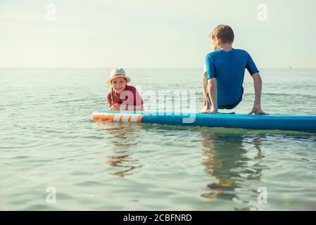 Due fratelli felici ragazzi in neoprene tute giocare e divertirsi con sup board in acqua nel Mar Baltico