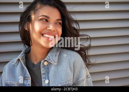 Sorridente giovane afroamericana teen girl guardando via ridendo, headshot. Foto Stock