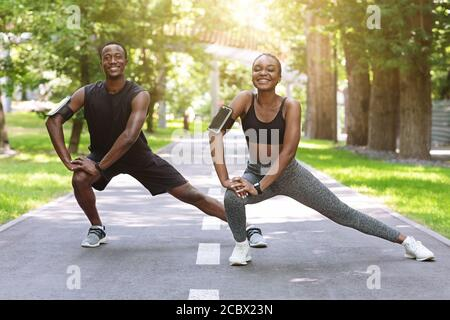 Coppia Black Runner che stretizza i muscoli all'aperto, si scalda prima di fare jogging a Park Foto Stock