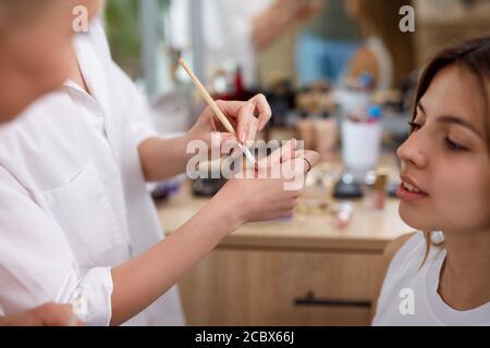 il professionista make-up artista o visagist applica i cosmetici a portata di mano prima di applicarli sul viso, in salone di bellezza