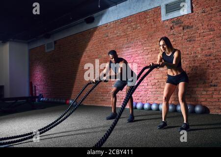 Coppia di famiglie interrazziali che si allenano con corde di battaglia in palestra. Donna caucasica che fa la corda di combattimento allenamento insieme con croce FIT African co