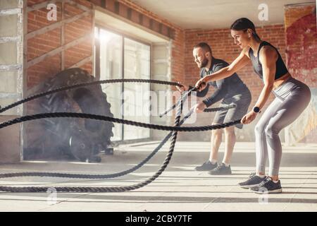 Montare caucasico giovane esercitando con battaglia corde in palestra. Donna e uomo vestito in abiti sportivi formazione insieme facendo combattendo la corda allenamento, con p
