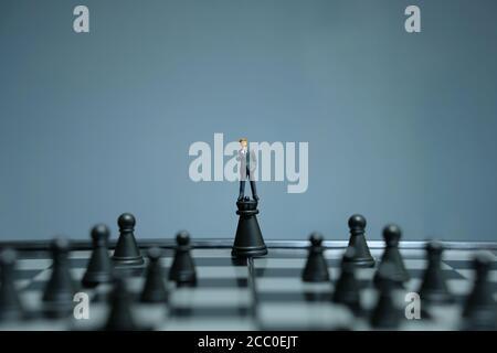 Strategia d'affari foto concettuale - uomo d'affari in miniatura in piedi sopra il castello pawn nel mezzo della scacchiera