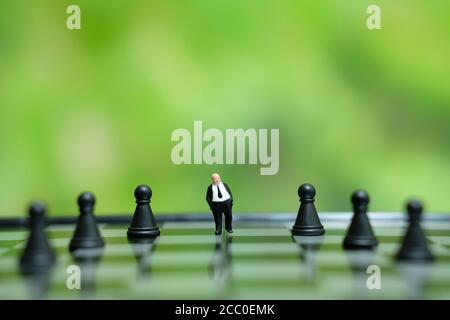 Foto concettuale strategia aziendale - miniatura di uomo d'affari in piedi la parte centrale del pezzo di scacchi su una scacchiera