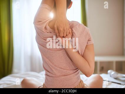 Vista posteriore della donna in t-shirt facendo esercizi di yoga sul letto in camera luminosa. Le mani siedono e schiena si bloccano meditando