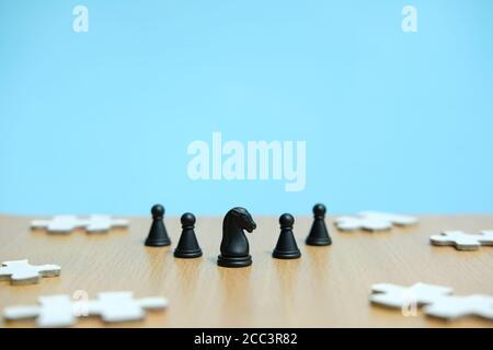Foto concettuale della strategia aziendale - una linea di cavallo pezzi di scacchi nel mezzo di un esercito e jigsaw puzzle