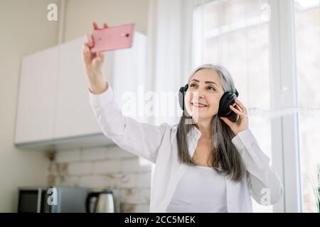 Bella donna con capelli grigi ritirata in camicia bianca in cucina, ascoltando musica in cuffia e utilizzando applicazioni multimediali su di lei