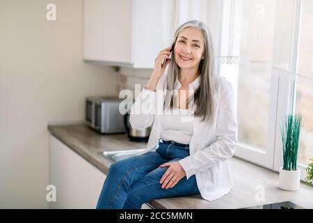 persone e tecnologie in pensione. Donna con capelli grigi molto allegri in camicia bianca e denim, che parla al telefono cellulare, mentre si siede sul