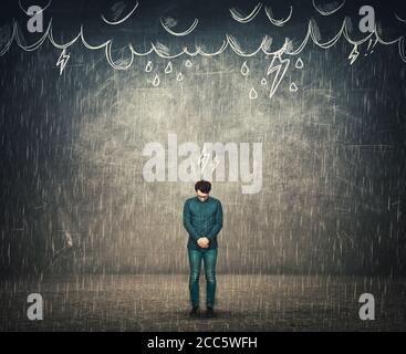 La depressione umana e il concetto di guasto emotivo, come uomo d'affari triste guarda giù deluso, non ha protezione ombrello mentre si trova sotto la pioggia,