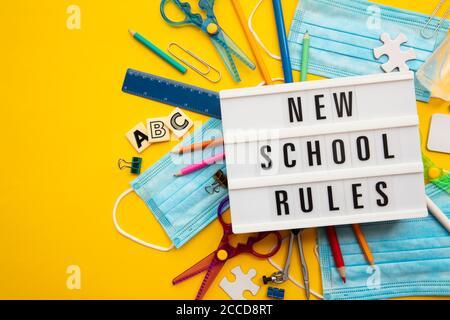 Nuovo messaggio di regole della scuola con attrezzature scolastiche e maschere di covid