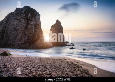 Tramonto a Ursa Beach Sea stack, Portogallo. Oceano Atlantico onde spumeggianti a rotolamento spiaggia di sabbia. Vacanza paesaggio scena. Foto Stock