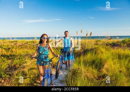 Estate gente stile di vita felice coppia in bicicletta sulla spiaggia rilassante attività all'aperto al tramonto. Giovane donna e uomo che cavalcano biciclette ricreative su Foto Stock