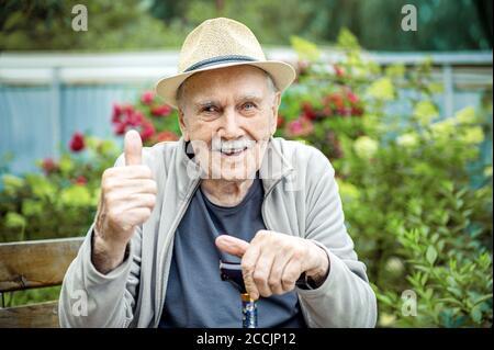 Ritratto di un anziano sorridente e sicuro 87 anni carino in un cappello con baffi. Felice anzianità attiva Foto Stock