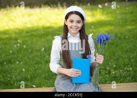 Elegante bambina scolastica con libro nel parco, concetto di biblioteca scolastica. Foto Stock