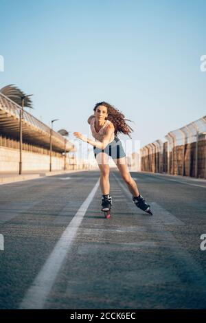 Giovane donna pattinaggio sul Boardwalk presso la costa