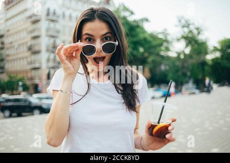 Sorpresa giovane donna con bocca aperta indossare occhiali da sole mentre si è in piedi sulla strada della città Foto Stock