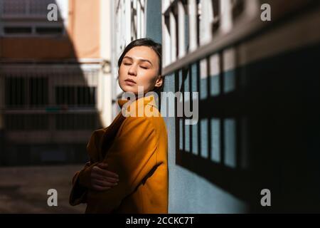 Giovane donna con gli occhi chiusi appoggiati al muro Foto Stock