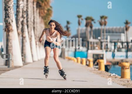 Giovane donna inline pattinare sul lungomare sulla costa
