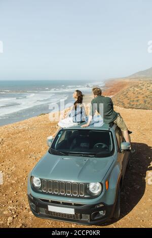 Concetto di viaggio su strada. Giovane e felice coppia hippie seduto sul tetto auto e godere di una fantastica vista sull'oceano e la costa del Marocco. Wanderlust e stile di vita.