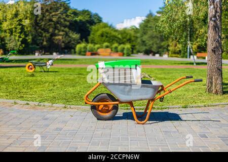 Carriola su un campo di erba verde. Carretto con carriola in metallo da giardino.