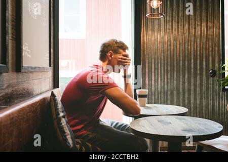 l'uomo sedette coprendo il viso sentendosi stressato mentre si sedeva un caffè