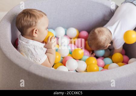Due adorabili bambini di 1 anno che giocano con palle colorate in un morbido playpen collocato sul parco giochi per bambini presso il centro giochi al coperto. Attività giocattoli f