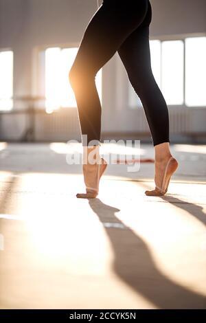 Foto delle gambe di una donna affascinante in piedi sulle punte delle zampe, ripresa dal basso, ripresa interna, concetto sportivo professionale
