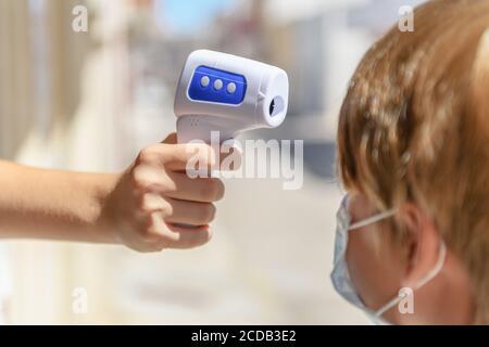 Termometro digitale che scannerizzazione la temperatura corporea di un bambino, nuovo normale ritorno a scuola.